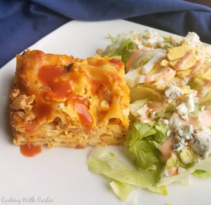 slice of creamy buffalo chicken lasagna on plate with blue cheese topped salad.