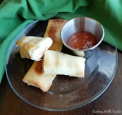 crab rangoon egg rolls with small container of sweet and sour sauce