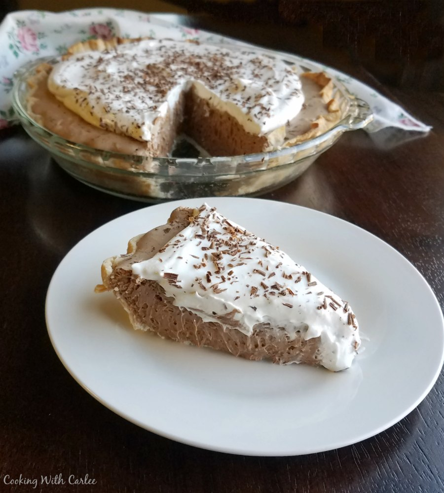 slice of french silk pie served on white plate with remaining pie in background.