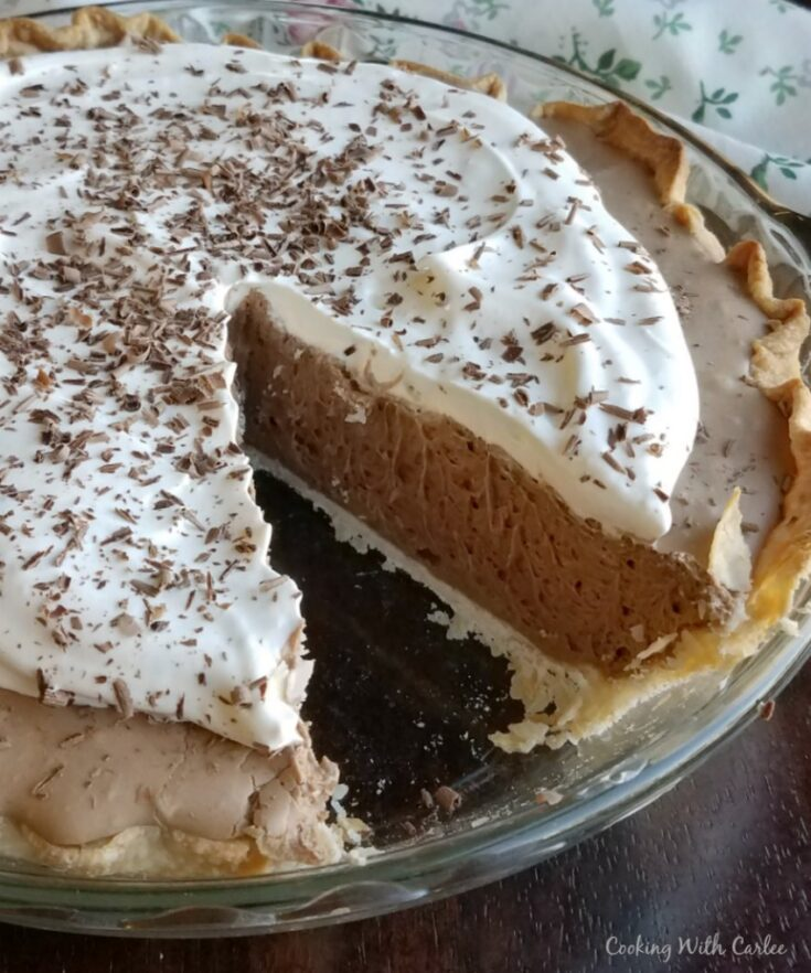 Chocolate french silk pie with whipped cream and chocolate shavings on top, one slice missing.