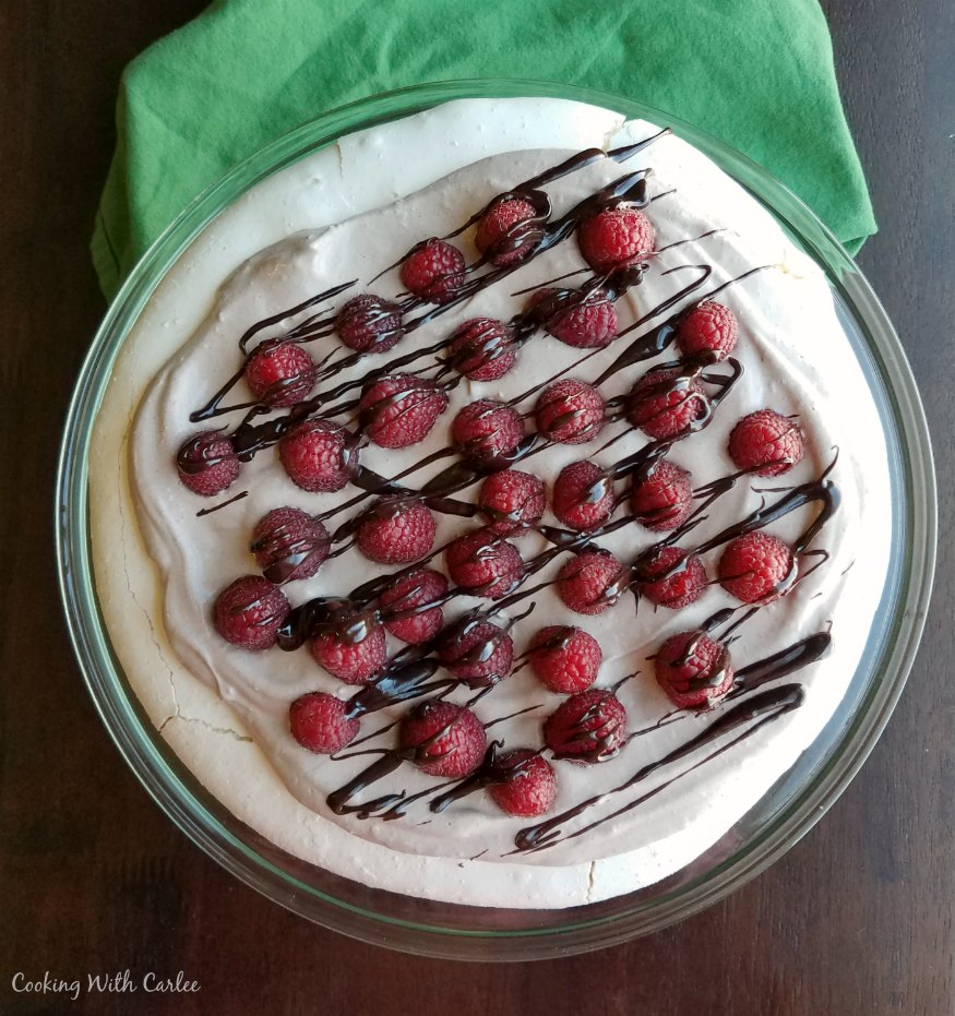 looking down on white pavlova with chocolate whipped cream, raspberries and drizzle of chocolate on top