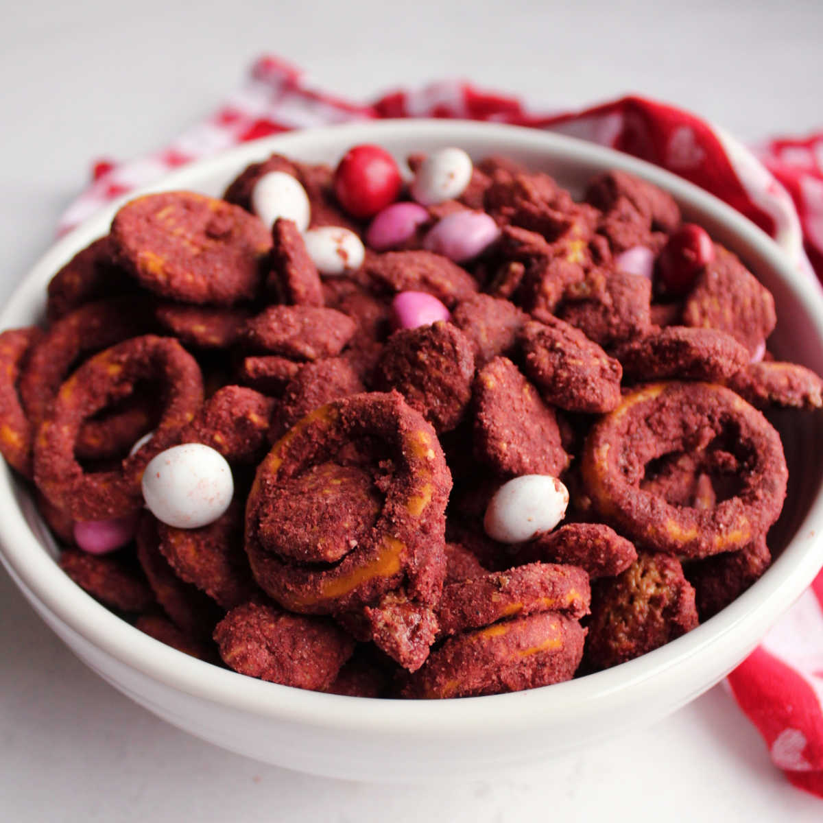 bowl of red velvet muddy buddies with pretzels and candies