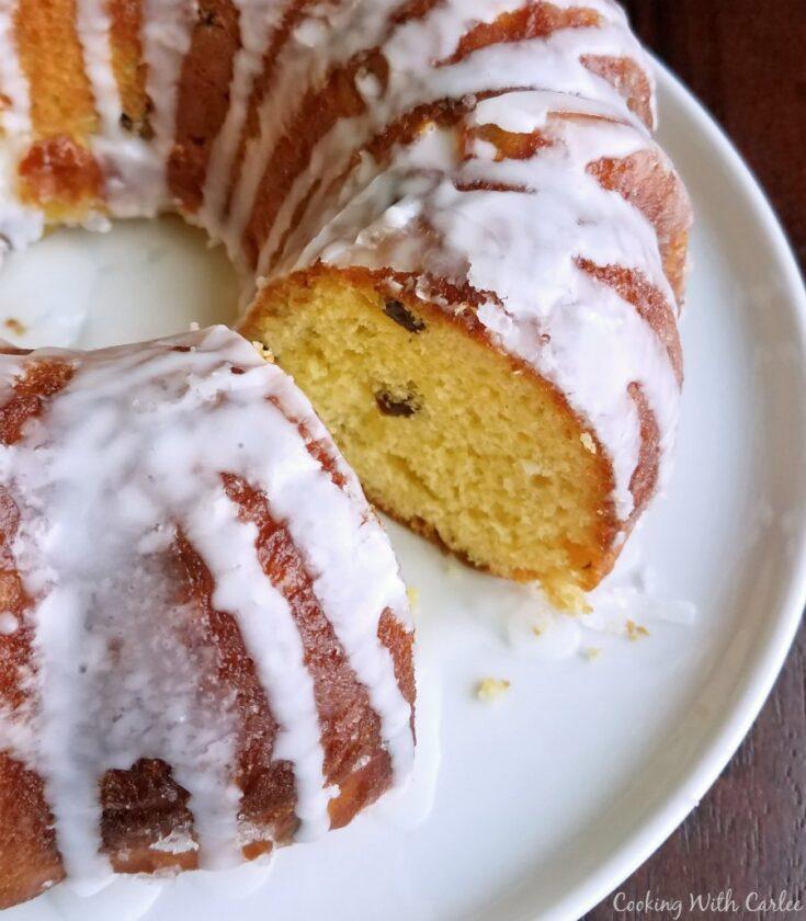 glazed lemon babka baked in bundt pan with slice missing showing soft yellow interior