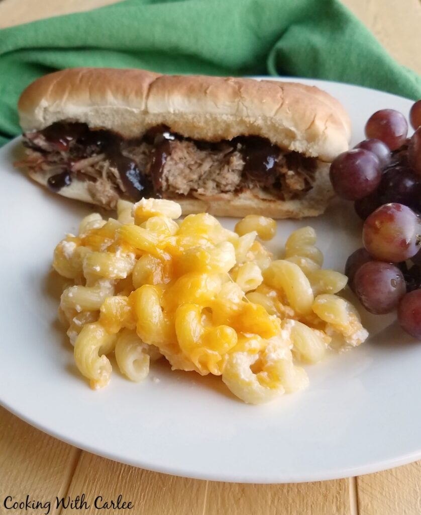 plate of mac and cheese with grapes and pulled pork sandwich.