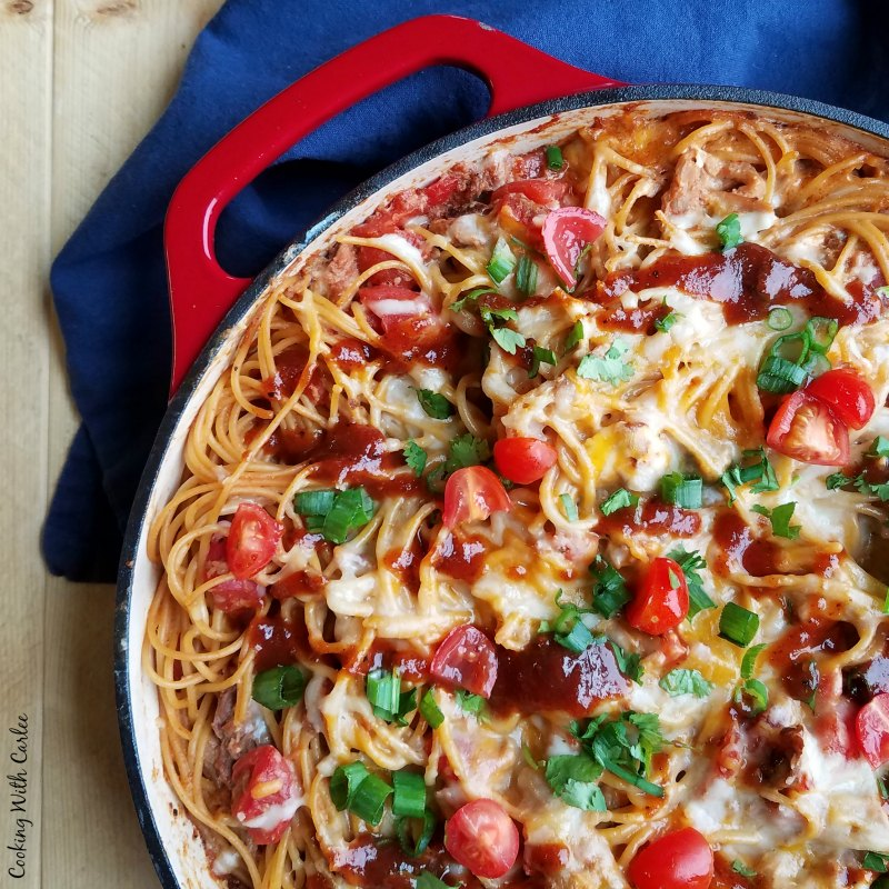 close up of enameled cast iron skillet full of creamy bbq pulled pork spaghetti with melted cheese, tomatoes, green onions and bbq sauce on top