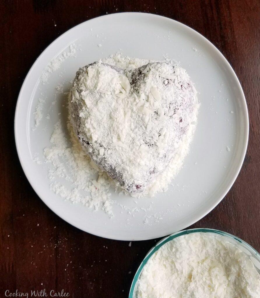 covering red velvet cheese ball in white chocolate shavings,