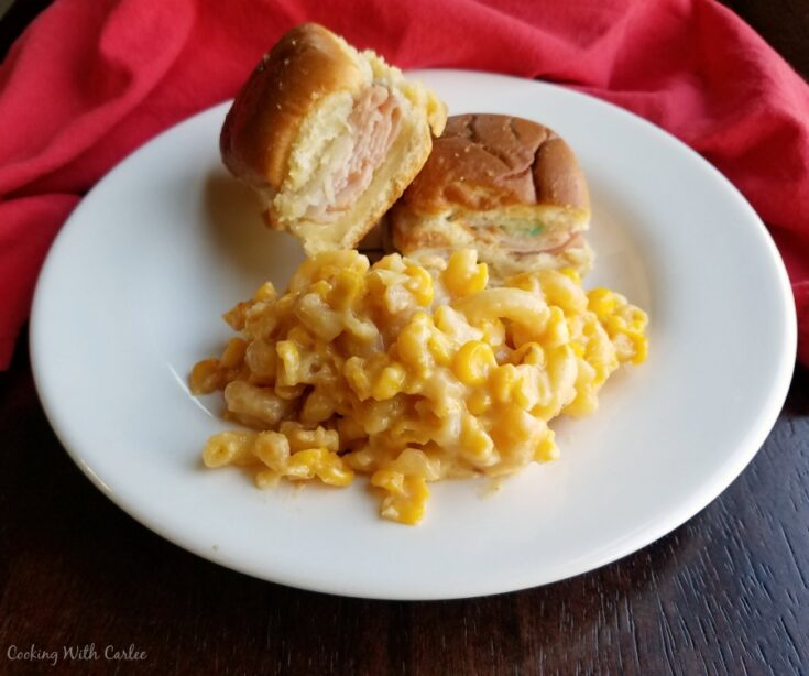 plate with pile of slow cooker macaroni and cheese with corn and hot ham and cheese sliders.