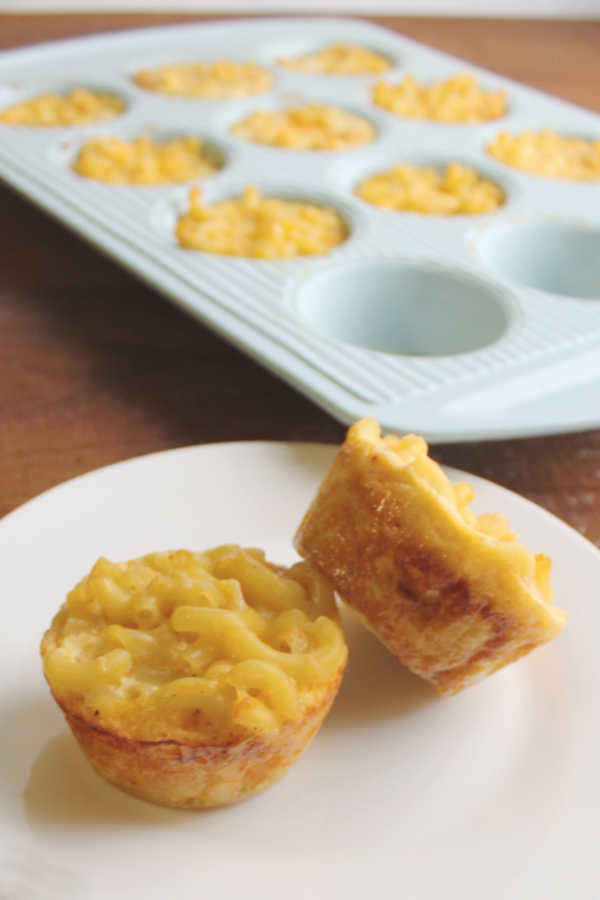 two macaroni and cheese muffins in front of muffin tin