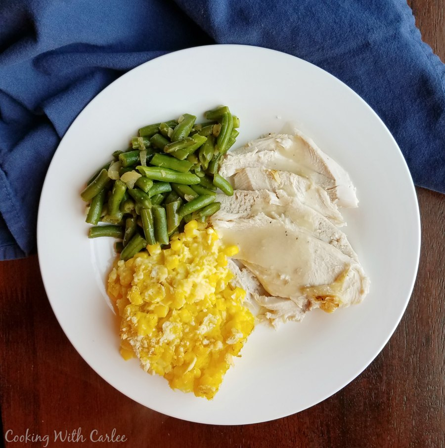 dinner plate with turkey, gravy, green beans and scalloped corn
