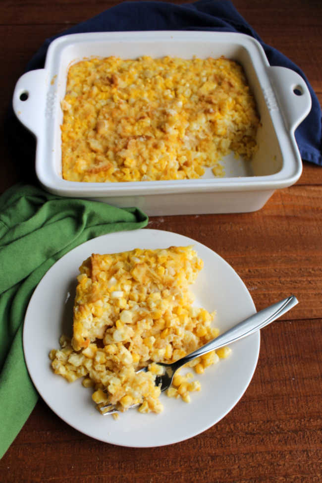 serving of old fashioned scalloped corn on plate with casserole in background