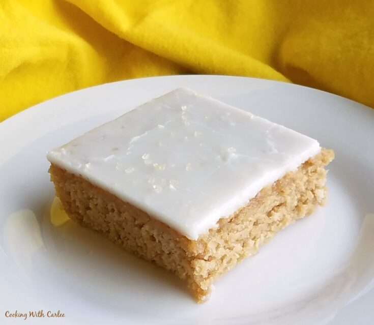 piece of sweet tea Texas sheet cake with lemon icing ready to eat