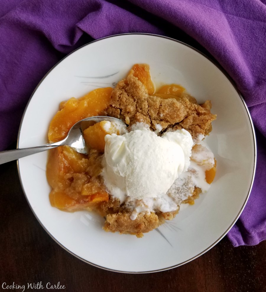 small bowl of golden peach cobbler with a scoop of vanilla ice cream
