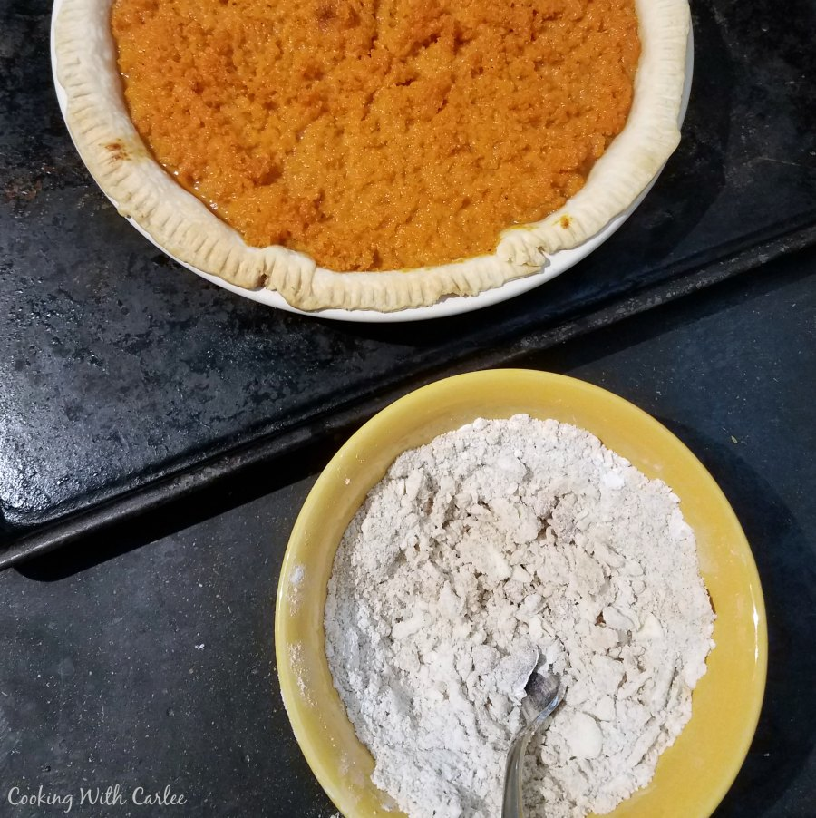pie plate filled with crust and carrot filling next to bowl of streusel topping,