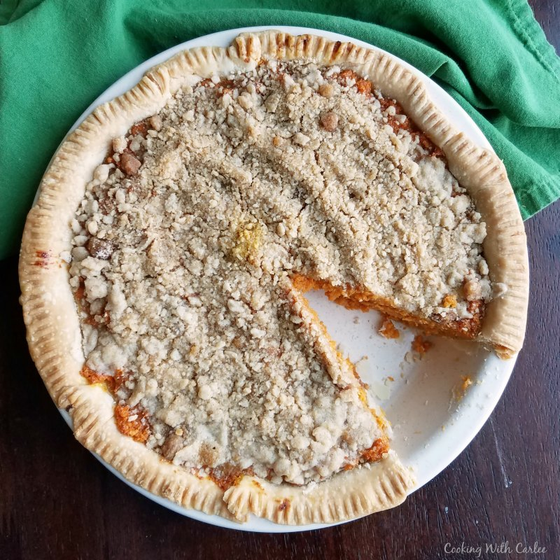 Carrot pie with buttery cinnamon crumb topping with one slice missing.