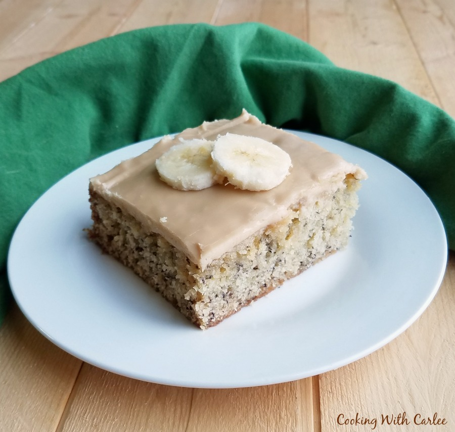 Slice of banana sheet cake with butterscotch frosting on top.