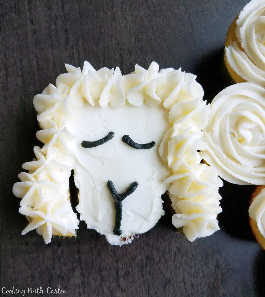 Close up of lamb face on cupcake cake.