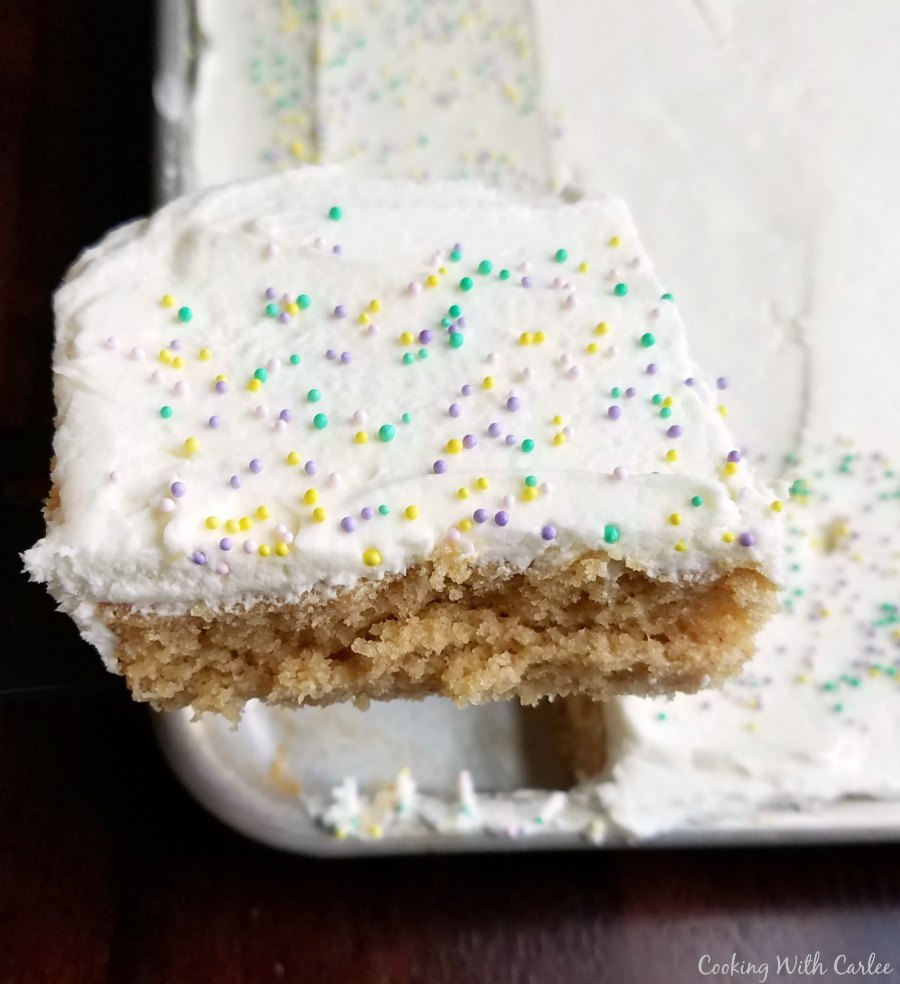 piece of frosted peanut butter sheet cake being lifted out of pan