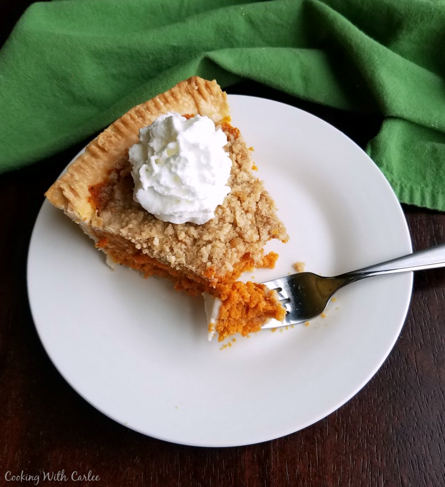 piece of carrot pie topped with whipped cream, first bite on fork.