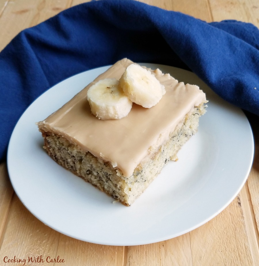 slice of banana cake with caramel icing and slices of banana on top with blue napkin in background.