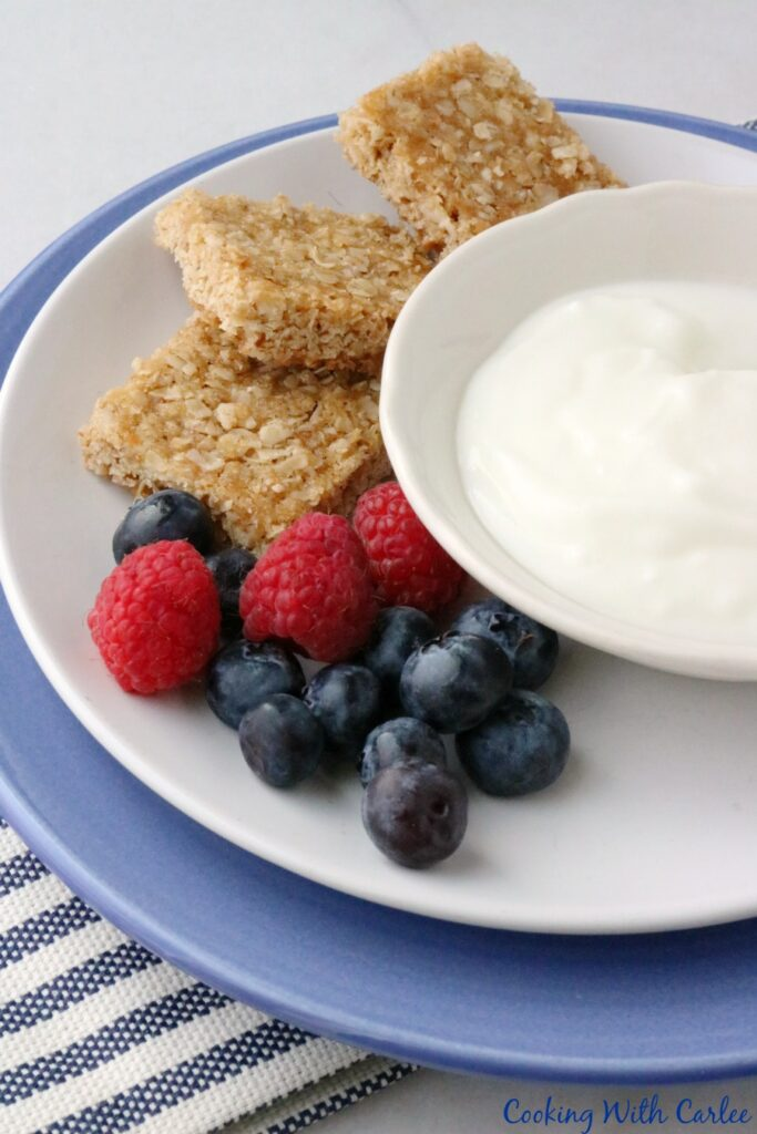 breakfast with berries, yogurt and oatmeal bars.