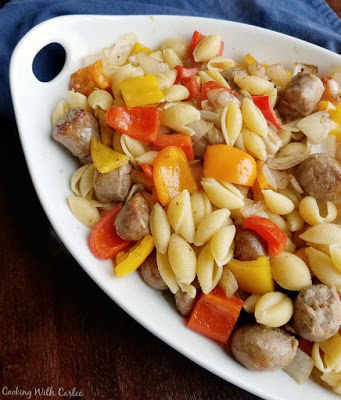 large serving dish filled with pasta tossed with sausage, peppers and onions