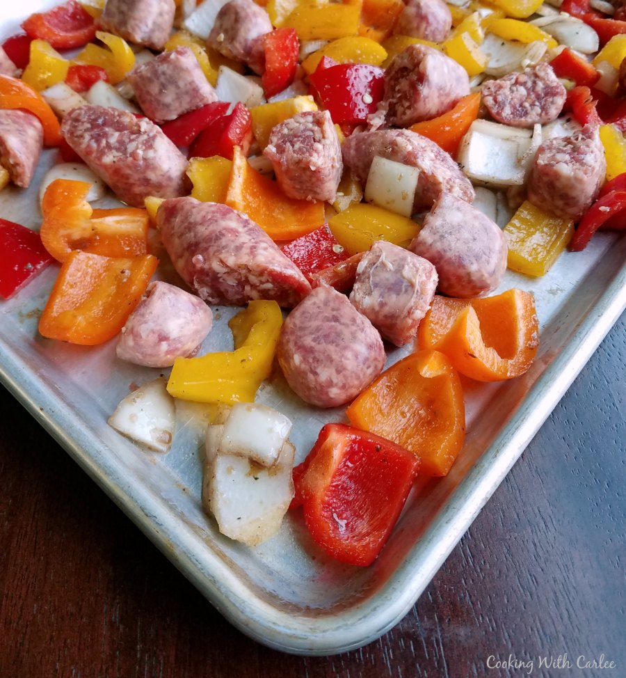 chunks of raw onion peppers and sausage on sheet pan ready to cook.