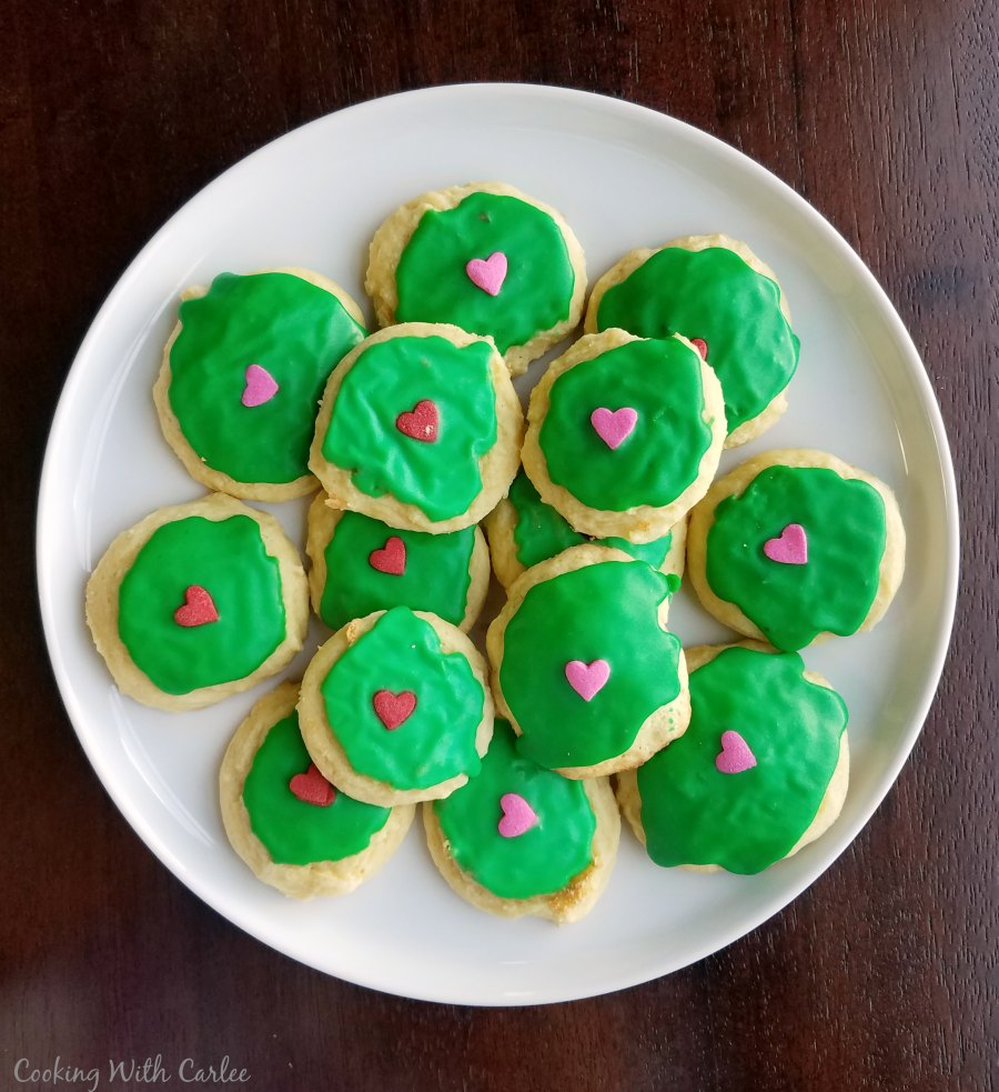 Sour cream cookies with green icing and candy hearts on top for Grinch cookies.
