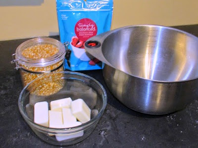 bowl of white chocolate, bag of freeze dried stawberries and container of popcorn next to big bowl