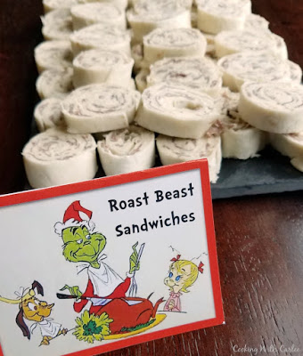 sign with The Grinch on it that say Roast Beast Sandwiches in front of pile of pinwheels