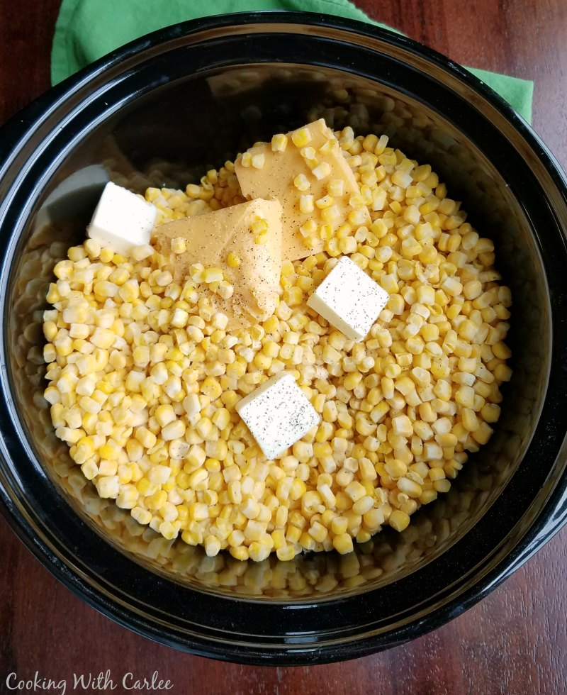 corn, butter and cheese in slow cooker crock.