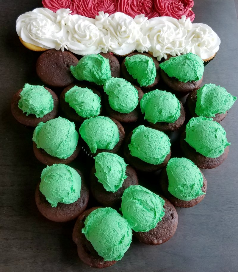 scoops of green frosting on chocolate cupcakes, ready to be smoothed out.