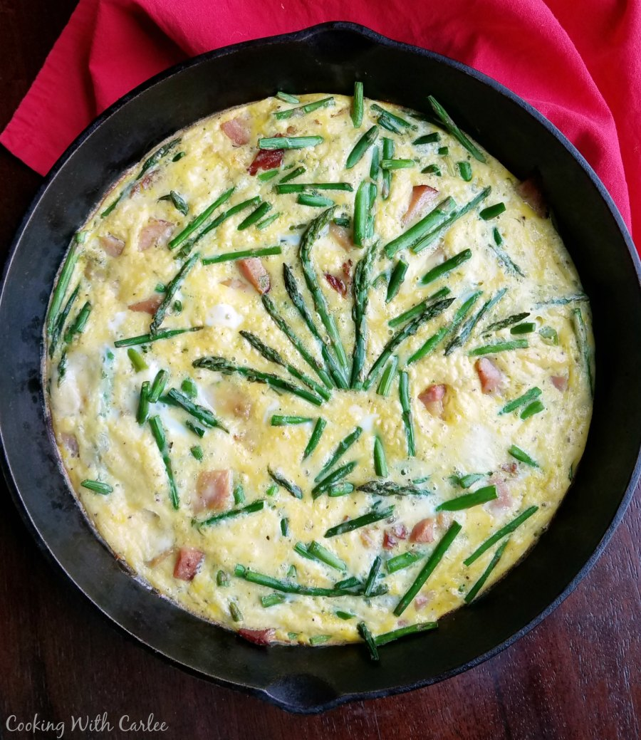 cast iron skillet full of frittata with eggs ham asparagus and cheese