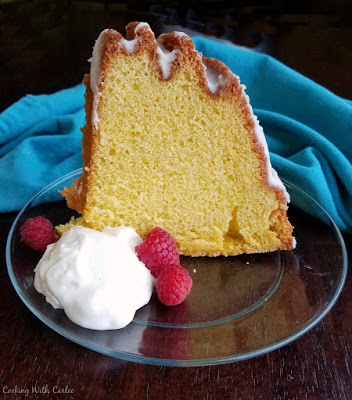 slice of yellow gold cake served with cream cheese whipped cream and raspberries