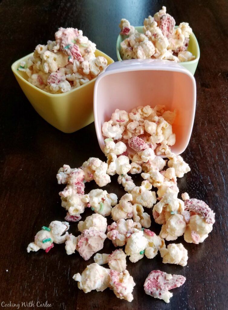 small bowls of strawberry and white chocolate popcorn spilled on counter.