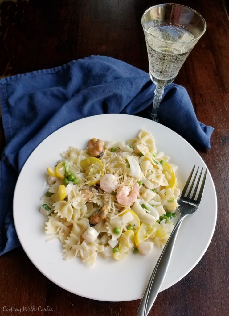 dinner plate of pasta primavera with a glass of white wine.