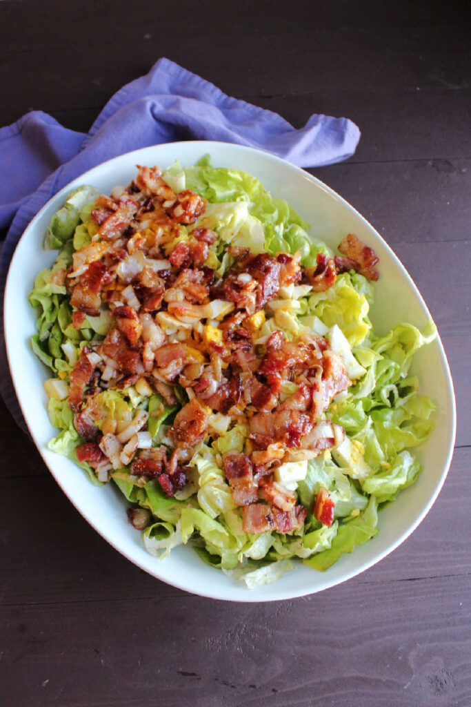 Bowl of lettuce topped with hard boiled eggs and warm bacon dressing ready to be tossed.