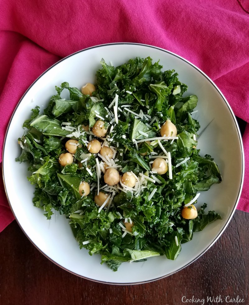 bowl of simple kale salad with lemon, chickpeas and Parmesan cheese.