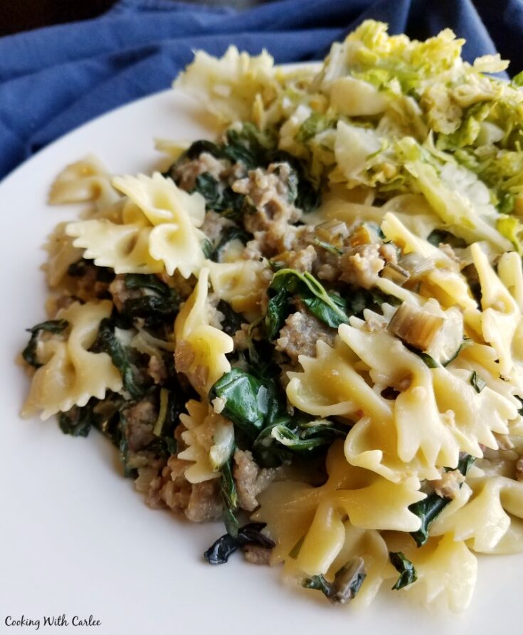 plate of creamy pasta with Italian sausage and wilted chard, ready to eat.