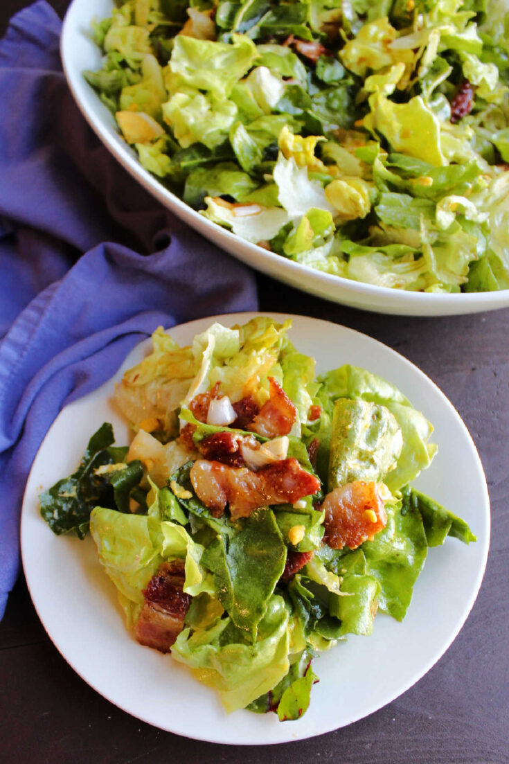 serving of wilted lettuce salad with bacon and hard boiled eggs.