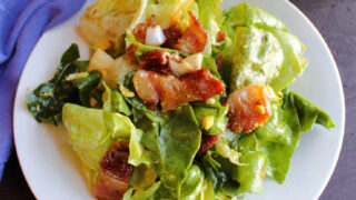 small plate piled high with wilted lettuce salad with big chunks of bacon and hard boiled egg mixed in.