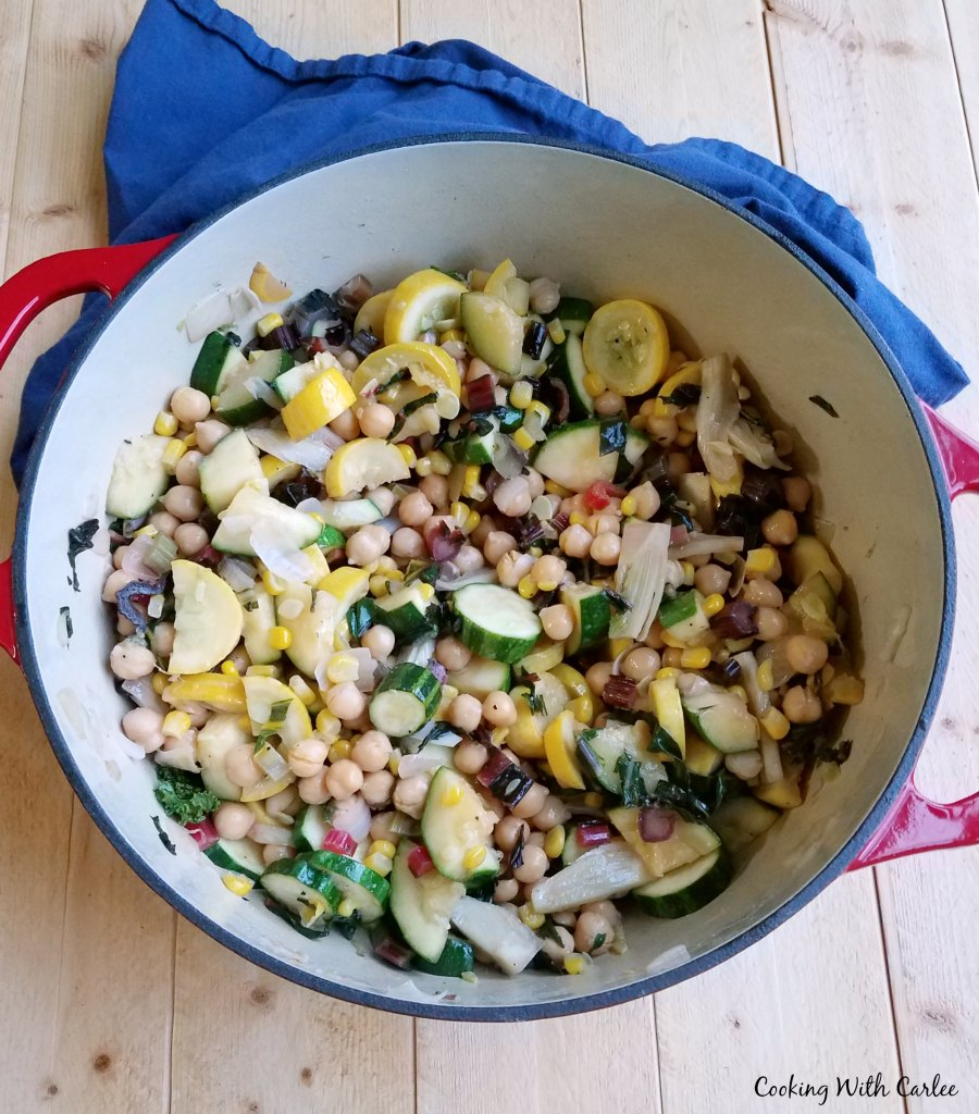 Dutch oven filled with a mix of zucchini, greens, corn and chickpeas to make a succotash style summer vegetable medley.
