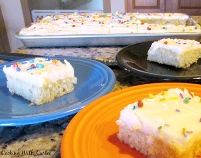several slices of white texas sheet cake served and various colors of Fiesta plates