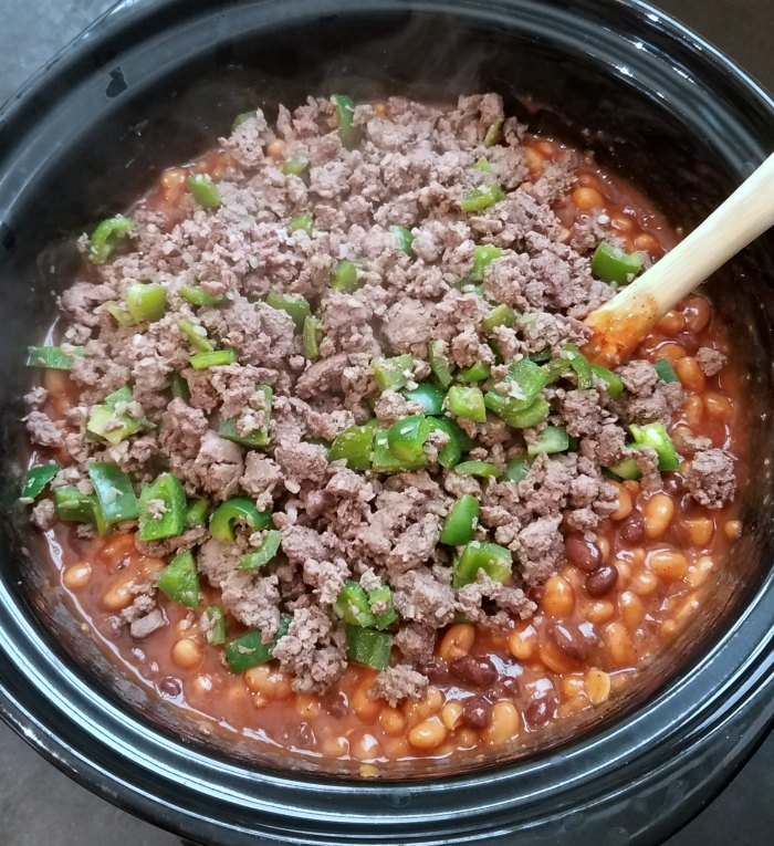 ground beef and diced green peppers on top of beans in slow cooker.