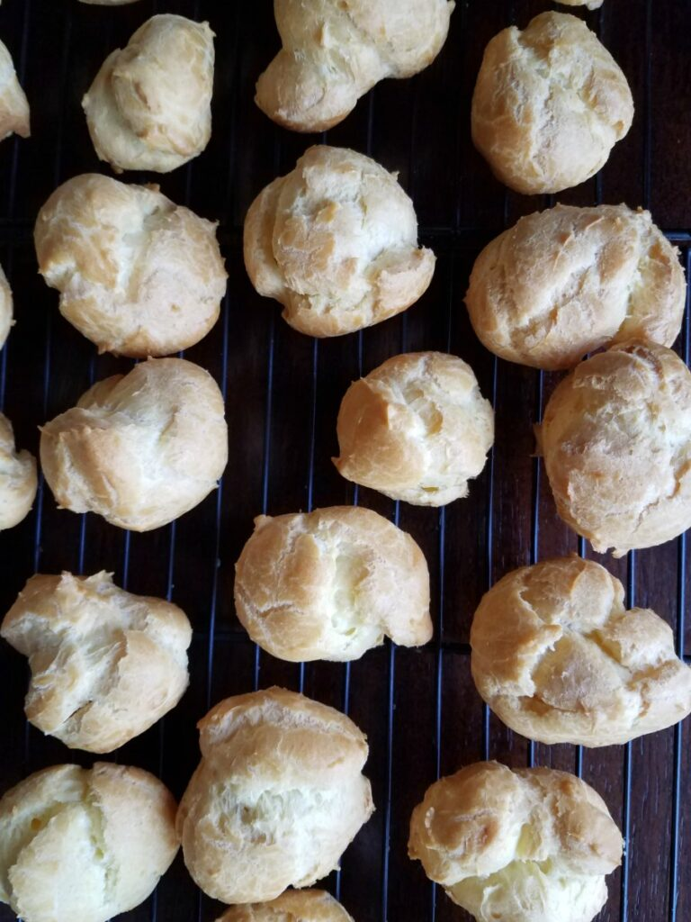 freshly baked cream puffs cooling on wire rack.