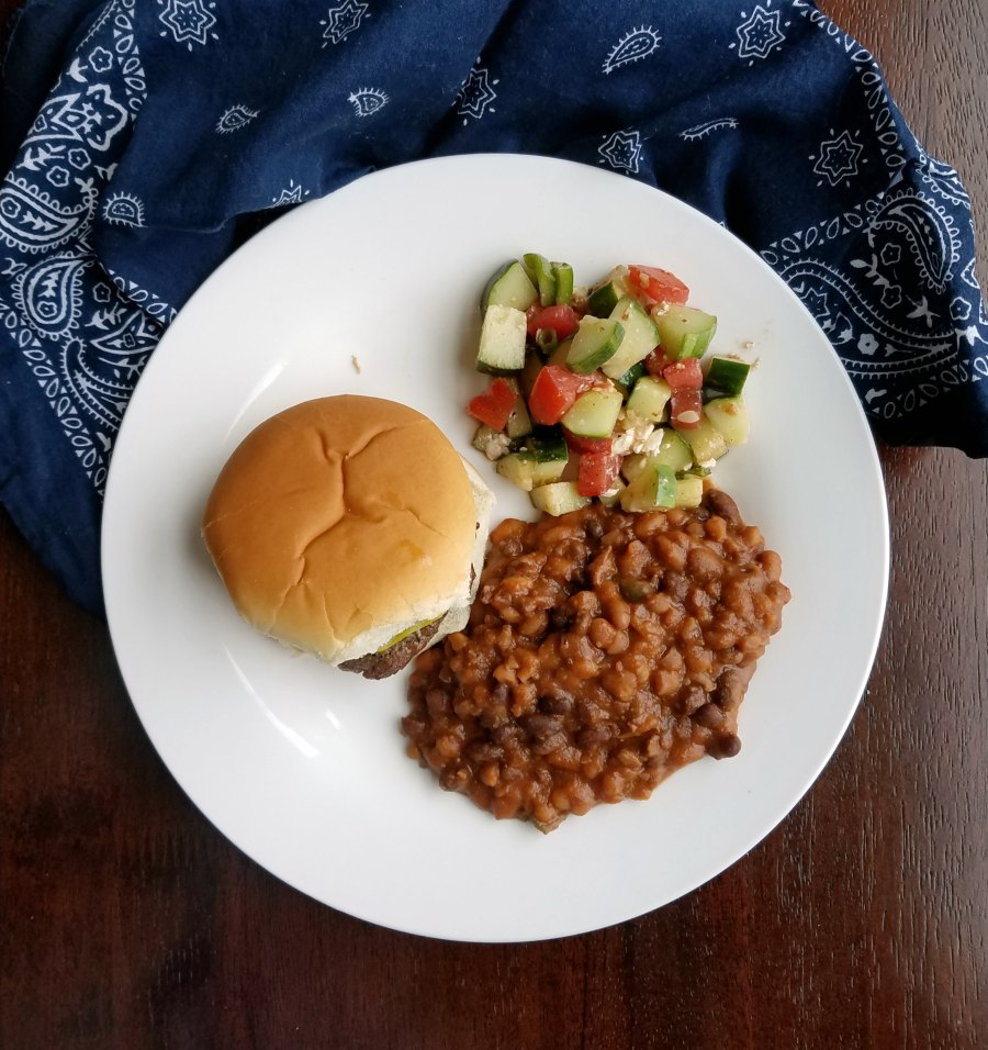 plate with burger, beans and tomato cucumber salad.