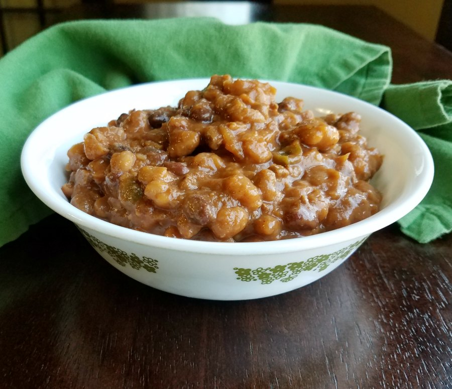 close up bowl of thick baked beans with meat