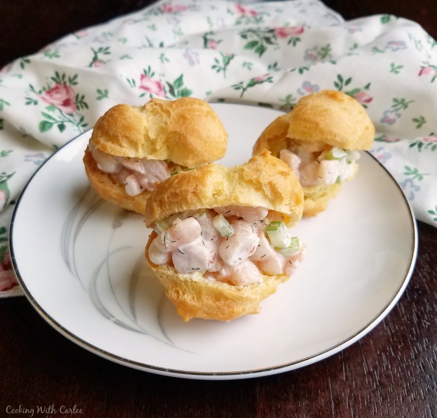 small plate filled with shrimp salad puffs ready to eat.