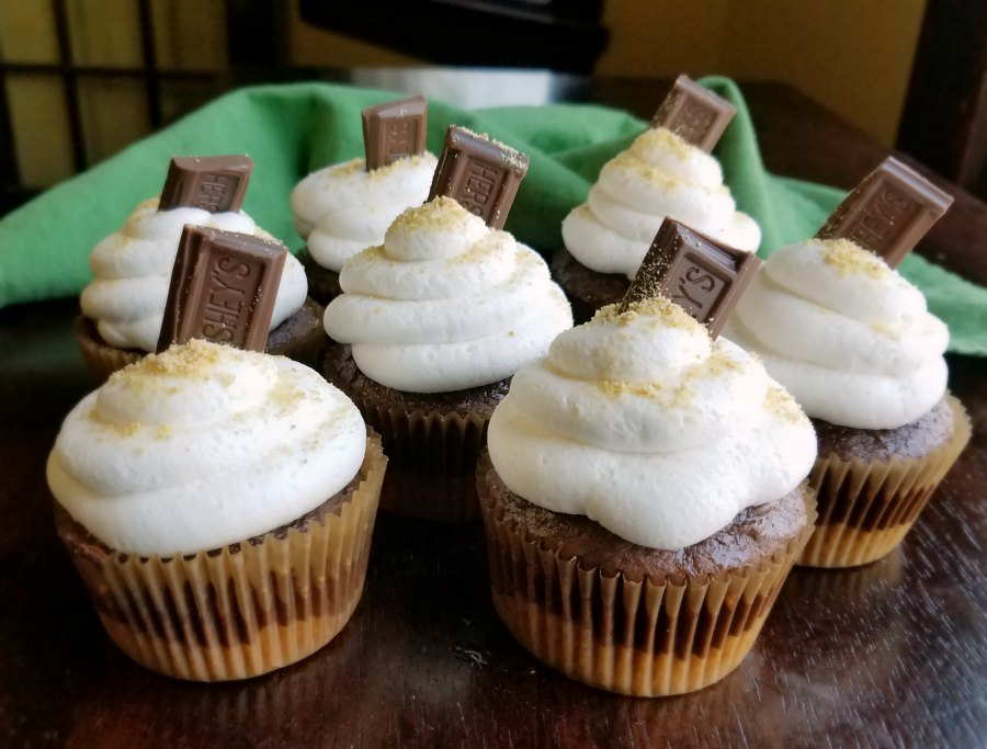 bunch of s'mores cupcakes with graham cracker crusts, chocolate cupcakes and toasted marshmallow frosting ready to eat