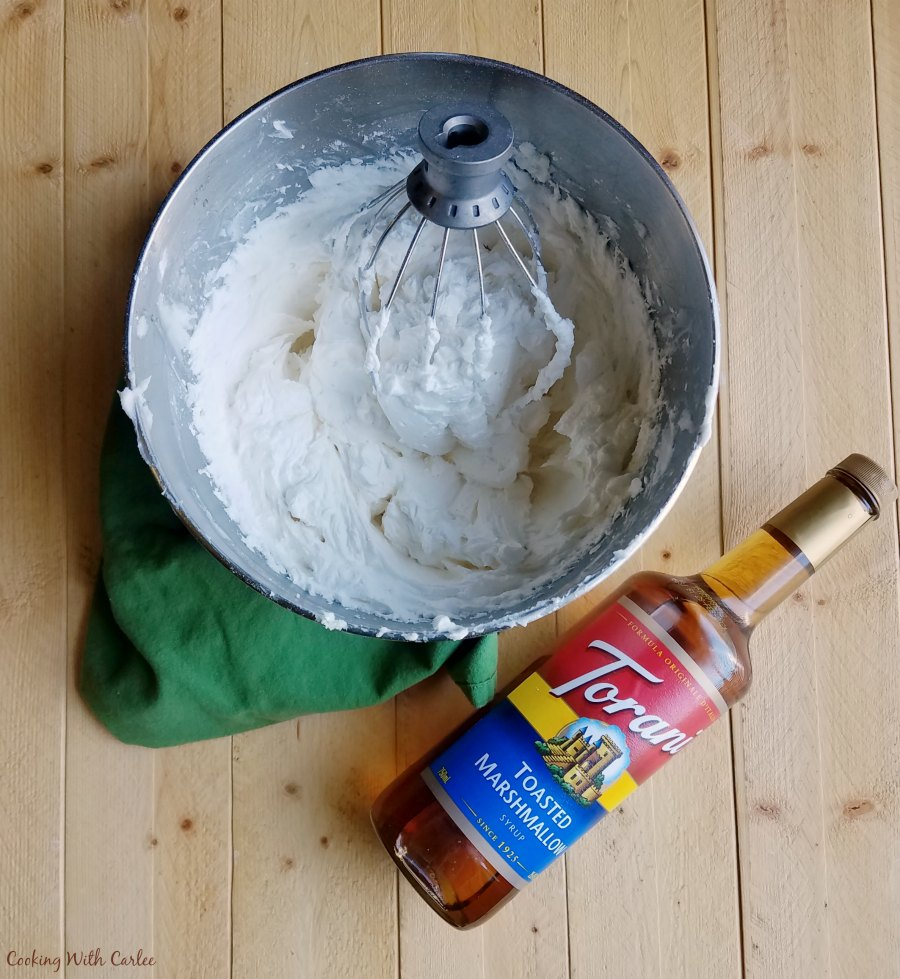mixer bowl of whipped cream and a bottle of flavored syrup