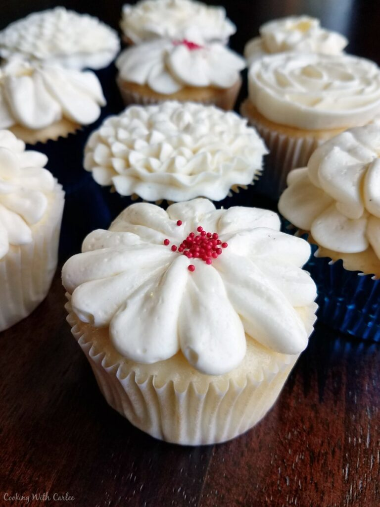 white cupcakes topped with Italian meringue buttercream flower decorations.